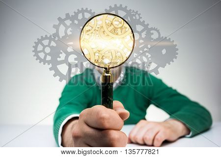 Search engine concept with man covering face with golden gear mechanism inside magnifier