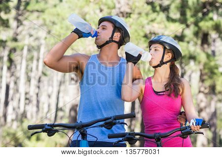 Young couple drinking water while riding bicycle at forest