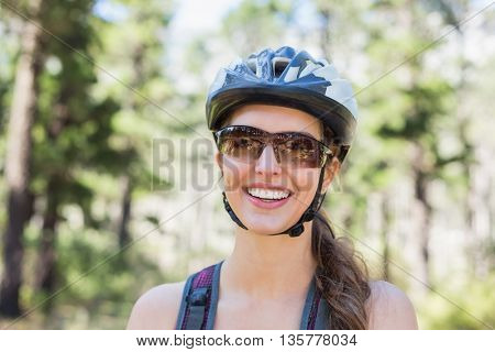 Portrait of happy woman wearing helmet against trees at forest
