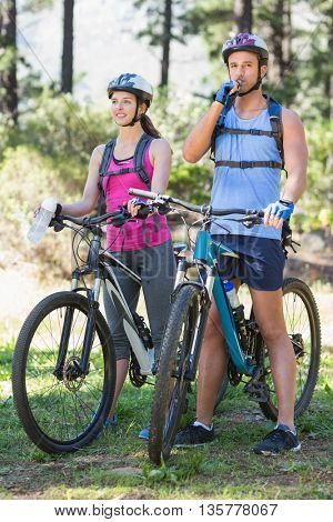 Young adventurous couple riding bicycle against trees at forest
