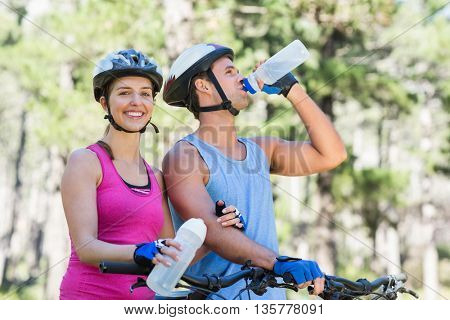 Portrait of young woman with man riding bicycle at forest