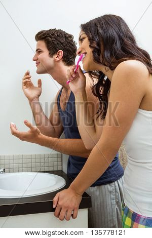 Couple in bathroom applying cream and brushing teeth in front of the mirror