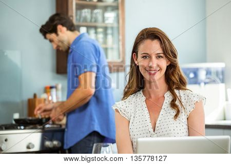 Portrait of woman with laptop in kitchen while man cooking food in background