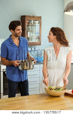 Happy young couple working in kitchen at home