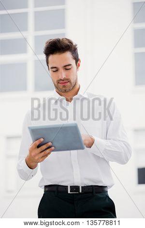 Businessman using a digital tablet on office terrace