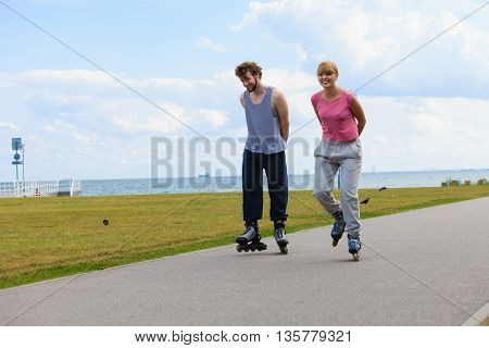 Love dating leisure romance relax concept. Cheerful couple enjoying ride together. Young girl and boy skating on rollerblades in park near sea.