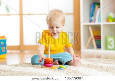 Preschooler child playing with colorful toy. Kid playing with educational wooden toy at kindergarten or daycare center. Toddler boy in nursery room.