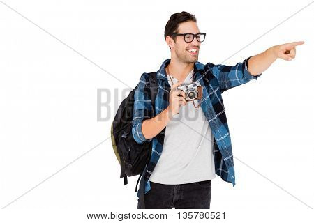 Young man carrying rucksack and holding camera on white background