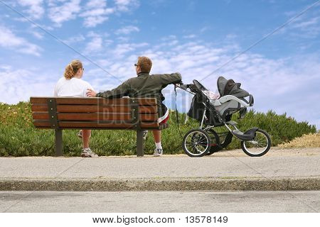 Mom and dad relaxing on a bench watching baby