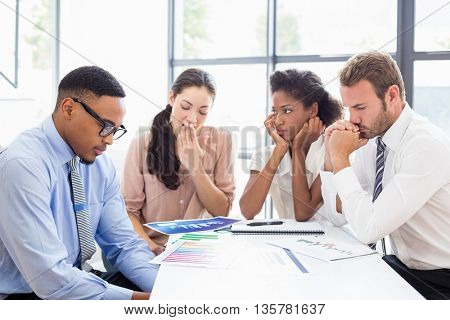 Tensed business people sitting at table during a meeting in office