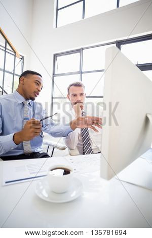 Businessmen looking at computer and interacting at a meeting in office