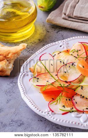 Vegetarian salad of carrot cucumber and radish selective focus.