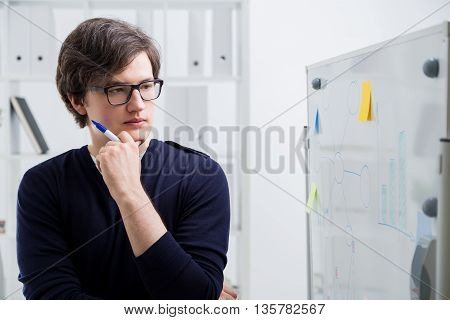 Attractive thoughtful young man looking at business charts drawn on office whiteboard