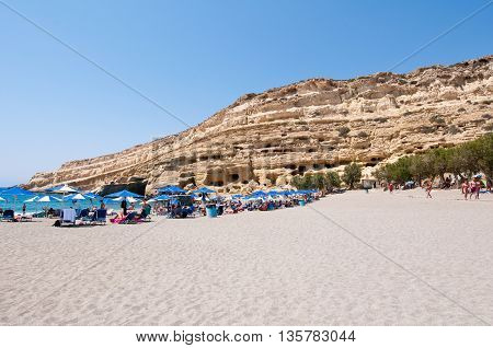 CRETE GREECE-JULY 22: Holidaymakers on Matala beach with the caves on July 222014 Crete Greece.
