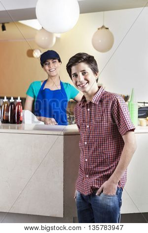 Confident Boy With Hand In Pocket Standing With Waitress