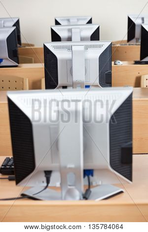 Computer Monitors On Desks In Classroom