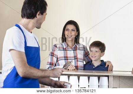 Waiter Serving Ice Cream To Happy Family