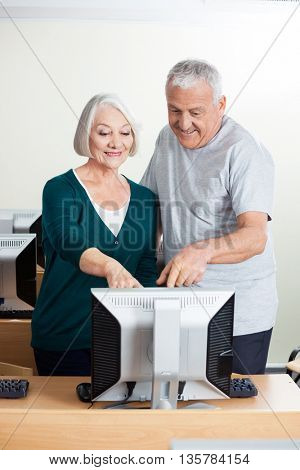 Happy Senior People Pointing At Computer Monitor In Class