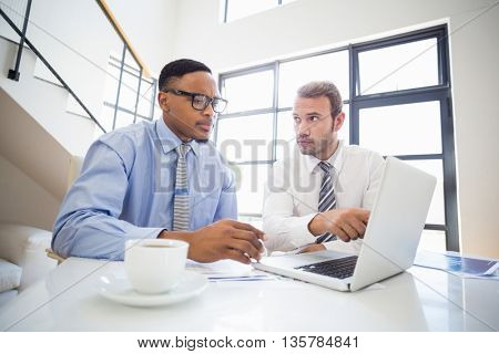 Businessmen looking at laptop and interacting at a meeting in office