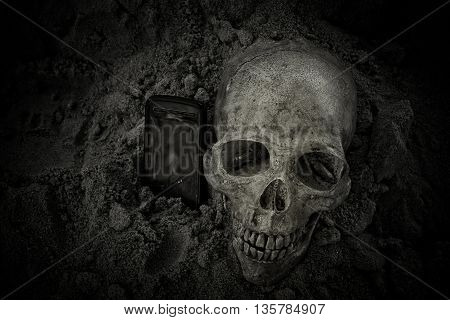 Still life with human skull and old mobile phone on sand background