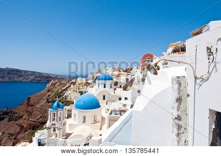 Churches with blue domes on the edge of the caldera on the island of Santorini Greece.