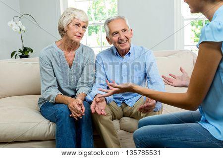Female consultant explaining senior couple while sitting on sofa at home