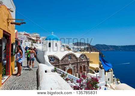 SANTORINIOIA-JULY 28: Tourists go shopping on July 282014 in Oia town on the Santorini island Greece. Oia is a small town on the islands of Thira (Santorini) and Therasia in the Cyclades Greece.