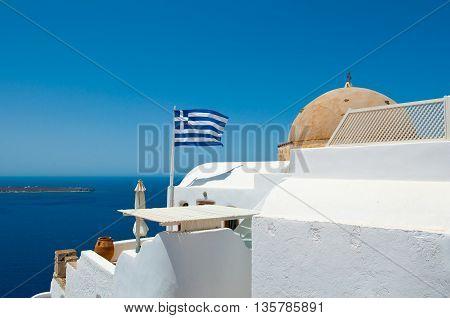 Oia Orthodox church and Greek flag on the edge of the Santorini caldera cliff on the island of Thira (Santorini) Greece.