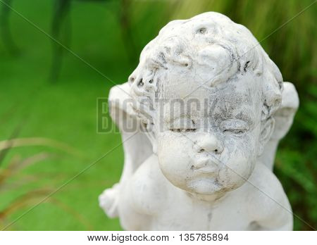 head shot stone sculpture cupid baby on green background