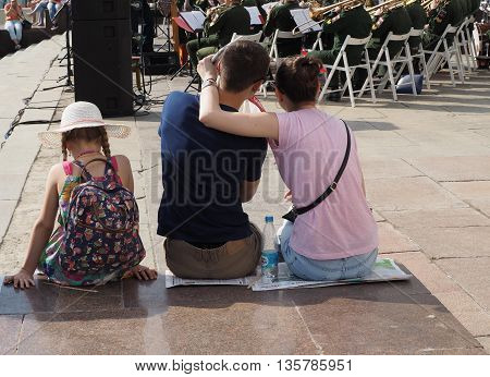 MOSCOW. RUSSIA - MAY 28, 2016: A pair of young men and a pre-adolescent girl seated on the parapet during a performance of the orchestra. Central Avenue in the Park of VDNH Moscow. International Military Music Festival