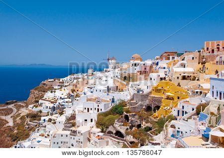Colorful Oia town on the edge of the caldera with windmills in the distance on the island of Thira (Santorini) Greece.