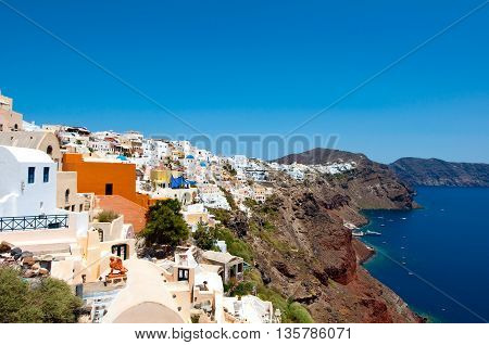 Oia traditional architecture with whitewashed buildings carved into the rock on the edge of the caldera on the island of Thera (Santorini) Greece.