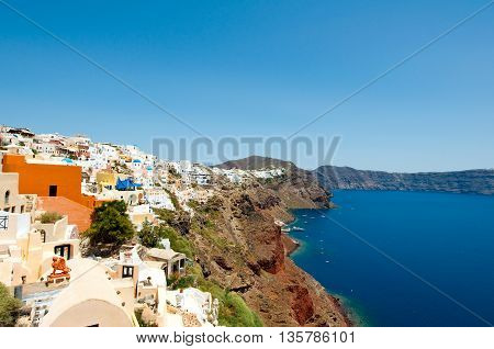 Oia town with whitewashed buildings carved into the rock on the edge of the caldera cliffs on the island of Thira (Santorini) Greece.