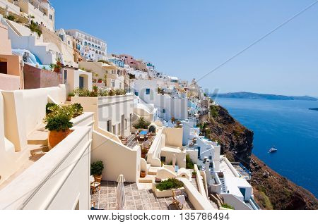 Fira traditional architecture with whitewashed buildings carved into the rock on the edge of the caldera cliff on the island of Thira (Santorini) Greece.