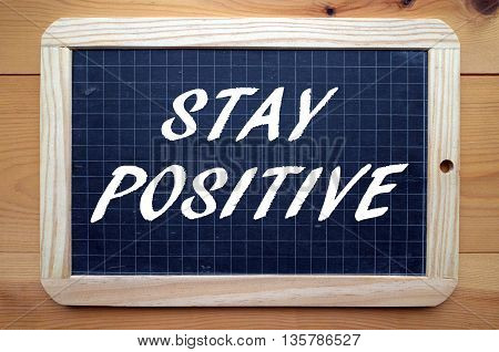 The words Stay Positive written in white text on a blackboard as a reminder