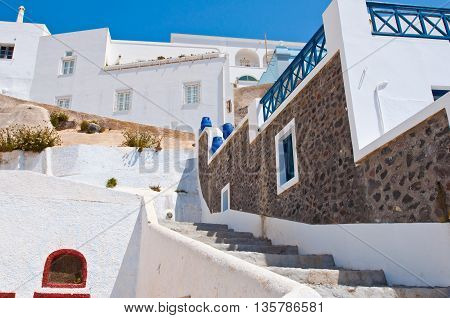 Fira street with whitewashed and blue houses on the island of Thira (Santorini) Greece.