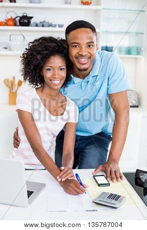 Portrait of young couple using laptop while calculating bills