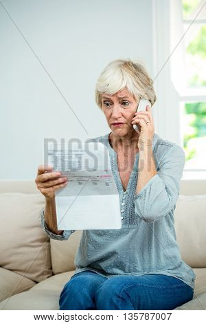 Aged woman reading document while talking on phone in living room at home