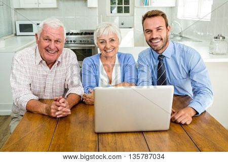 Portrait smiling senior couple sitting with agent at home