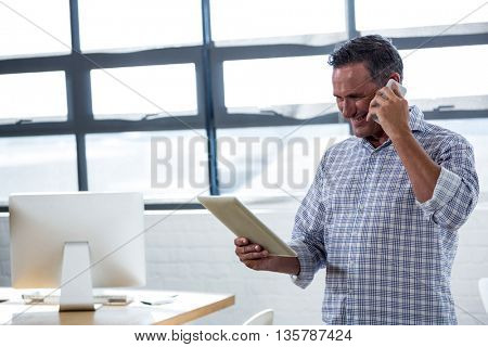Man looking at digital tablet while talking on phone in office