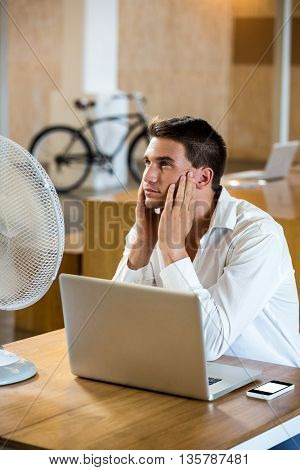 Man enjoying a breeze with laptop at desk in office