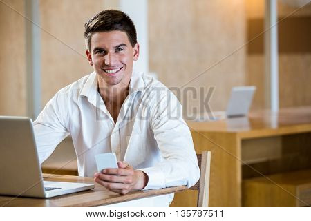 Portrait of man holding mobile phone and laptop on a desk in office