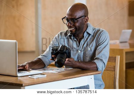 Man holding camera while using laptop in office