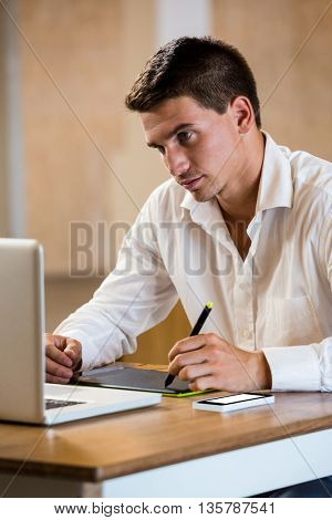 Man working on his graphics tablet in office
