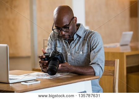 Man in office sitting at desk checking photo in camera with laptop