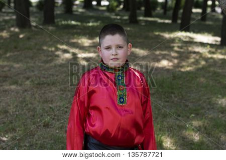 the boy in the Russian shirt against the wood a subject people and holidays