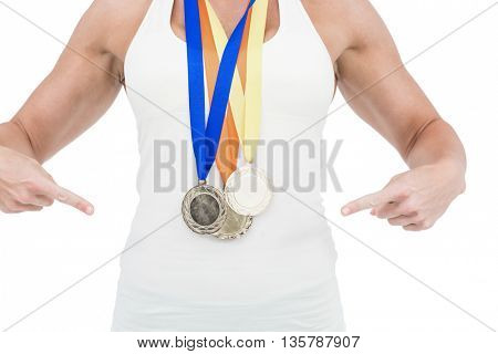 Female athlete pointing her medals on white background
