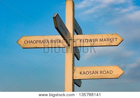 Bangkok street sign with directions to Chaopraya river Kaosan road flower market and Chinatown with blue sky on the background. Travel directory pointer with copy space