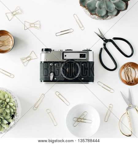feminini desk workspace with succulent retro camera scissors and golden clips on white background. flat lay top view