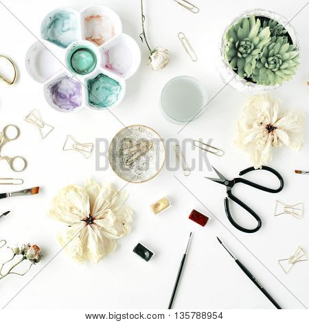 flat lay composition with bow tie clips scissors dry tulip roses palette succulent on white background. top view
